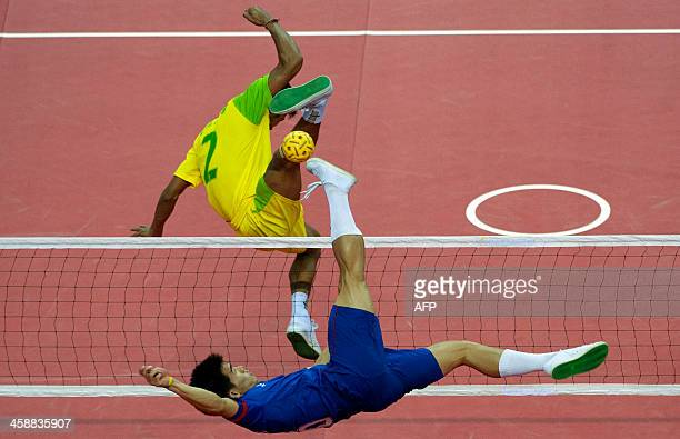Lao's Noum Souvannadee returns the ball to Zaw Zaw Aung of Myanmar during the men's double team sepaktakraw final at the 27th Southeast Asian SEA...
