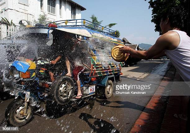 Laos people splash water on a TUK TUK during the Songkran festival during the Songkran festival on April 15 in Luang Prabang Laos The Songkran...