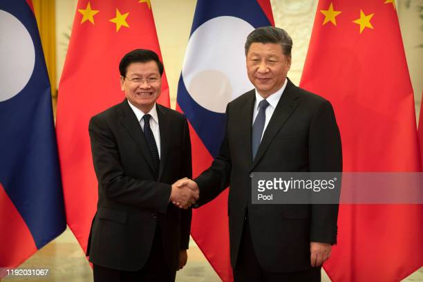 Laos Prime Minister Thongloun Sisoulith left and Chinese President Xi Jinping shake hands before a meeting at the Great Hall of the People on January...