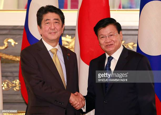 Laos' Prime Minister Thongloun Sisoulith shakes hands with his Japanese counterpart Shinzo Abe prior to a meeting at Akasaka Palace state guesthouse...