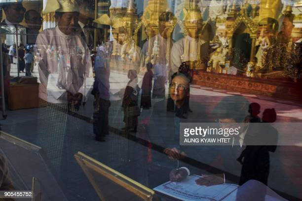 TOPSHOT Laos Prime Minister Thongloun Sisoulith signs a visitors' book inside a room overlooking the iconic stupa at the renowned Shwedagon Pagoda in...