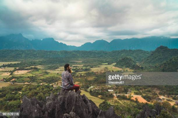 Laos, Vang Vieng, hiker sitting on rock, looking at distance