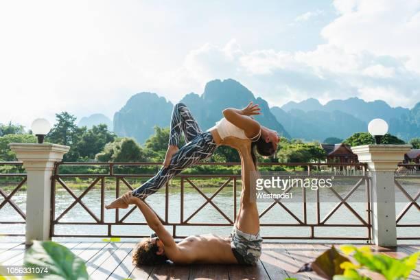 Laos, Vang Vieng, Young couple doing acro-yoga on a terrace
