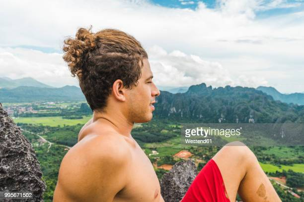 Laos, Vang Vieng, young man on top of rocks overlooking landscape of rice fields
