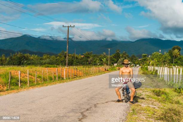 Laos, Vang Vieng, young man with bicycle in the road