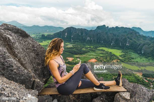 Laos, Vang Vieng, young woman on top of rocks using cell phone