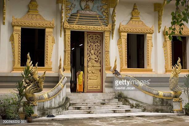 Laos, Vientiane, monk sweeping steps of wat (temple)