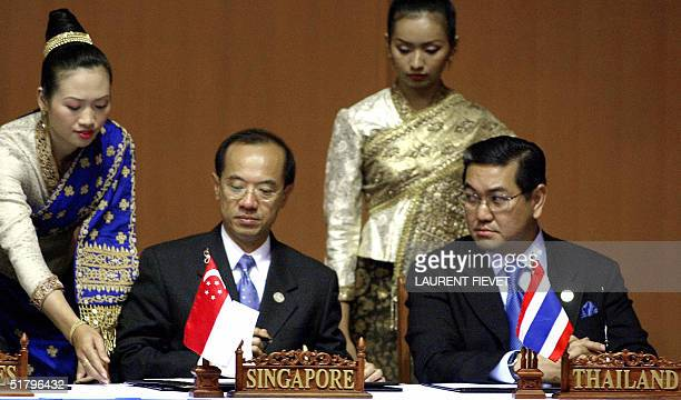 A Laotian attendant in a traditional dress hands a document to Singaporean Foreign Minister Geirge Yeo while his Thai counterpart Surakiart...