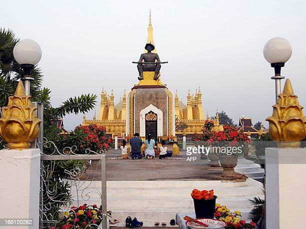 A Laotian family prays and makes offerings at the statue of King Setthathirat in front of the main stupa Pha That Luang in Vientiane 05 December 2004...