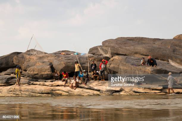 laotian fishermen sitting and setting up net traps from mekong river bank - laotian culture stock pictures, royalty-free photos & images