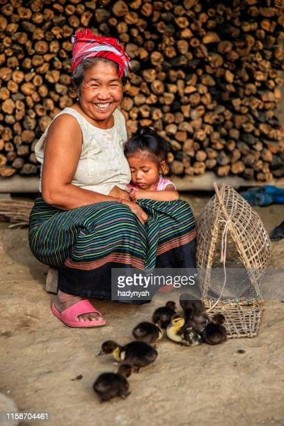 laotian grandmother sitting with little girl in a village in northern laos - laotian culture stock pictures, royalty-free photos & images
