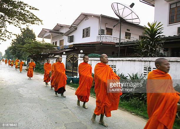 Laotian khuubaa walk past a house with a satellite dish during their early daily alms round in Vientiane 06 December 2004 The first monarch of Laos...