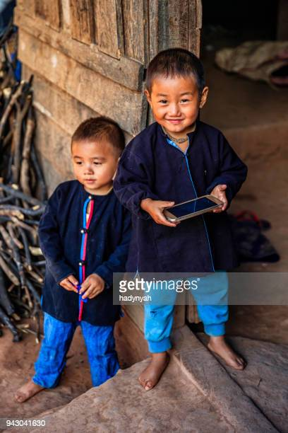laotian little boys playing on smartphone, village in northern laos - electrical equipment stock photos and pictures