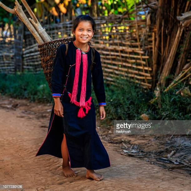laotian little girl carrying a wood in a village in northern laos - laotian culture stock pictures, royalty-free photos & images
