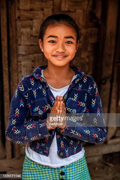 laotiska lilla flicka säger sabaidi i en by i norra laos - prayer pose greeting bildbanksfoton och bilder