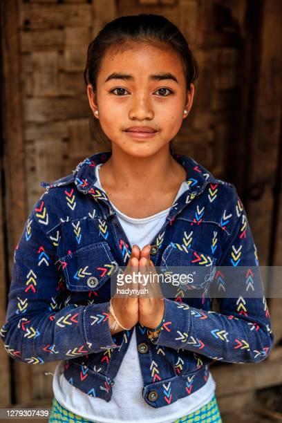 laotiska liten flicka säger sabaidi i en by i norra laos - prayer pose greeting bildbanksfoton och bilder