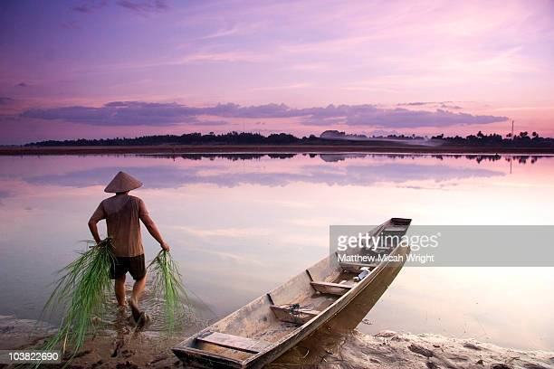 Laotian man walking into calm river near canoe.