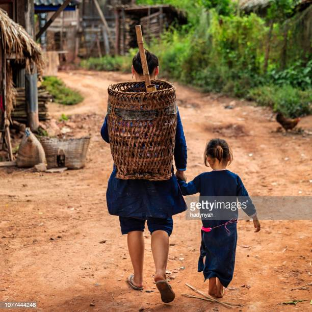 laotian mom walking with her daughter in a village in northern laos - laotian culture stock pictures, royalty-free photos & images