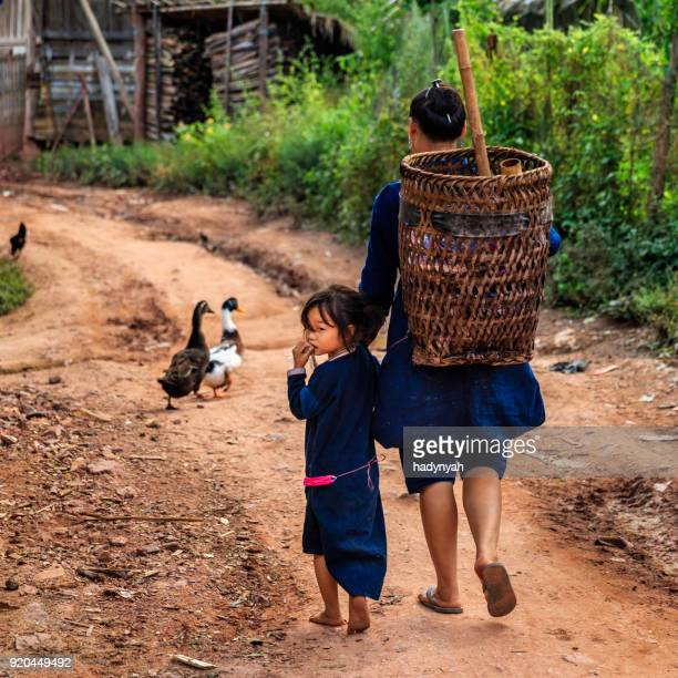 Laotian mom walking with her daughter in a village in Northern Laos