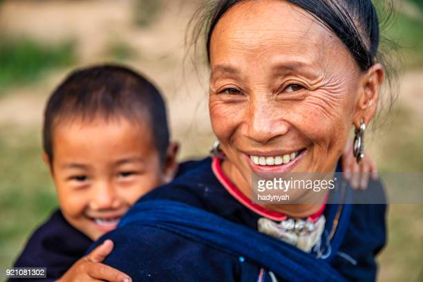 Laotian mother carrying her little son, village in Northern Laos