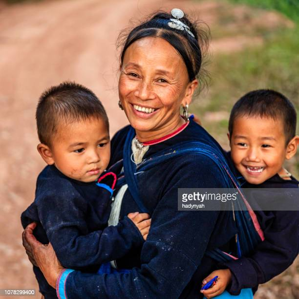 laotian mother walking with her children in a village in northern laos - laotian culture stock pictures, royalty-free photos & images