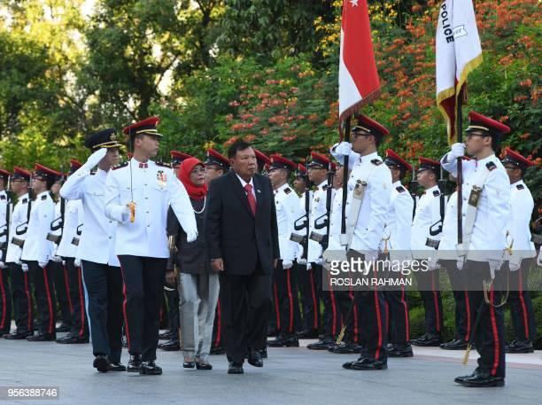 Laotian President Bounnhang Vorachith followed by Singaporean President Halimah Yacob inspects a guard of honour during a welcoming ceremony at the...