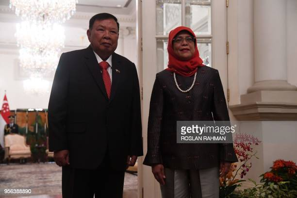 Laotian President Bounnhang Vorachith poses with Singaporean President Halimah Yacob after a welcoming ceremony at the Istana presidential palace in...