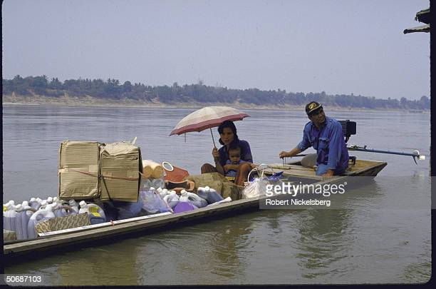 Laotian traders leaving in boats loaded with Thai goods purchased at a market on the Mekong River