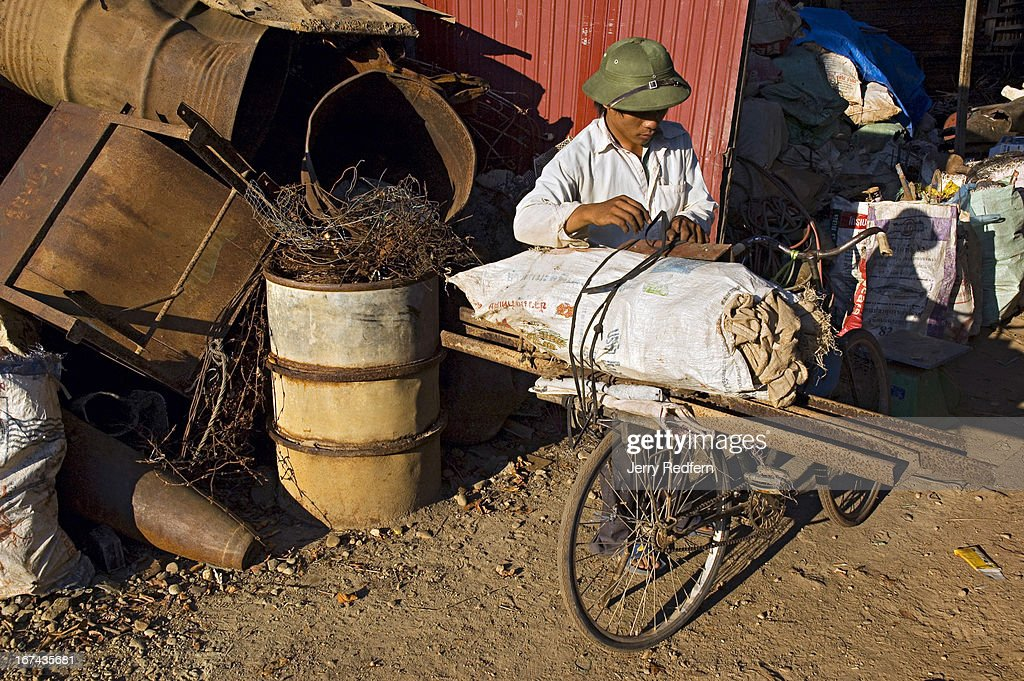 A Laotian unloads a sack full of bomb shrapnel and other war detritus at a scrap metal shop. Behind him a defused 500-pound bomb pokes out from a pile of odd and ends. The shop owner buys all manner of war scrap from locals who collect it in the surrounding forests; he then sells truckloads of scrap to Vietnamese traders who take it to their country to resell. The US heavily bombed the surrounding area during the war, which left a vast amount of bomb scrap and UXO (unexploded ordnance) that locals have incorporated into their daily lives..