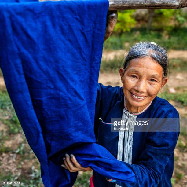 Laotian woman checking freshly dyed fabric in a village in Northern Laos