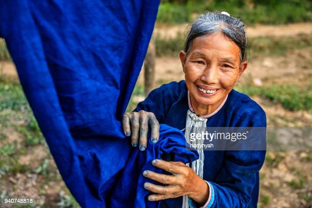 laotian woman checking freshly dyed fabric in a village in northern laos - navy blue stock pictures, royalty-free photos & images