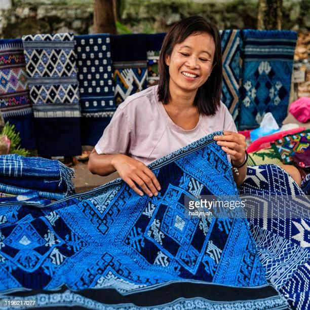 朝市で伝統的な織物を販売するラオス人女性、ルアンパバーン、ラオス - ラオス ストックフォトと画像