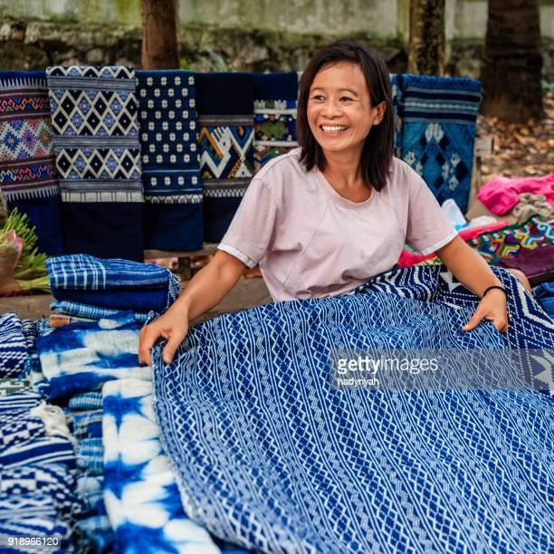 Laotian woman selling traditional textiles on a morning market, Luang Prabang, Laos
