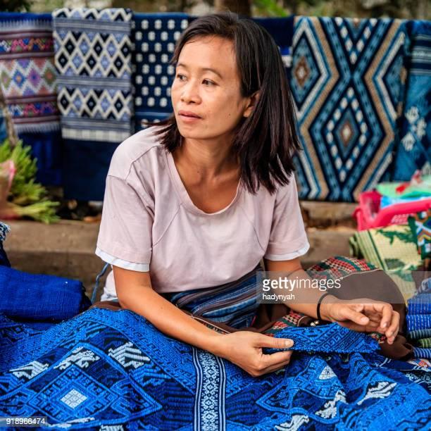Laotiaanse vrouw verkopen traditioneel textiel op een ochtend markt, Luang Prabang, Laos