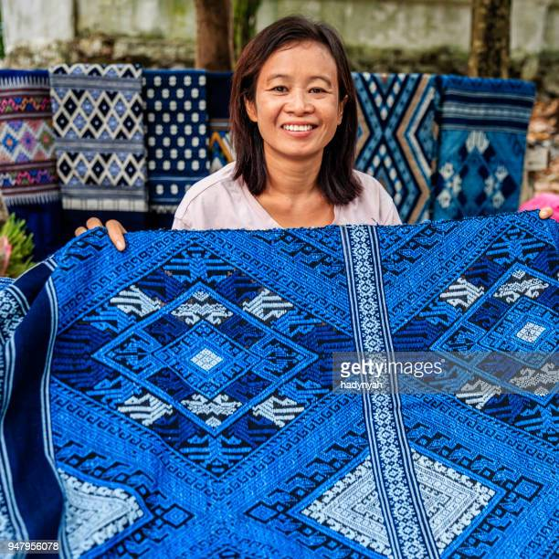 laotian woman selling traditional textiles on a morning market, luang prabang, laos - laotian culture stock pictures, royalty-free photos & images