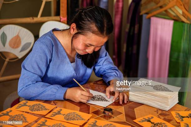 joven laosiana pintando postales en un taller, luang prabang, laos - laos fotografías e imágenes de stock