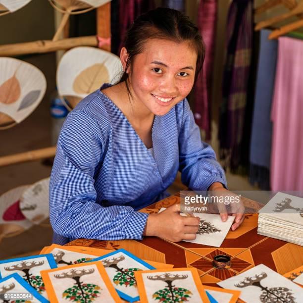 Laotiaanse jong meisje schilderij ansichtkaarten in een workshop, Luang Prabang, Laos
