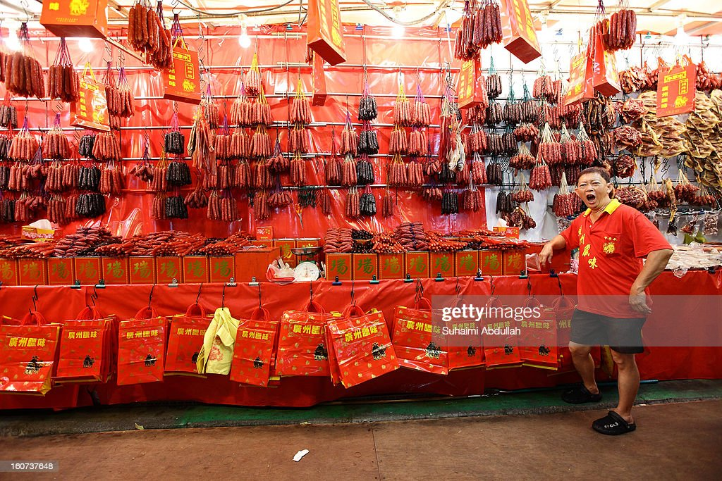 A lap cheong seller yawns as he waits for customers in Chinatown on February 4, 2013 in Singapore. On February 10th, Chinese around the world will welcome the Year of the Snake, one of the most anticipated holidays of the Chinese calendar. Also known as the Spring festival or the Lunar New Year, the celebrations last for about 15 days.
