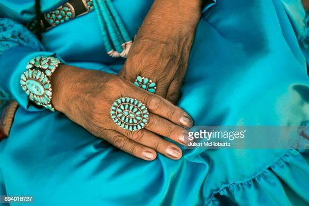 Lap of woman wearing traditional blue dress and rings