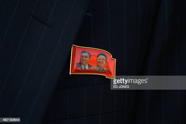 A lapel badge featuring portraits of former North Korean leaders Kim IlSun and Kim JongIl is worn by a spectator during a mass military parade at Kim...