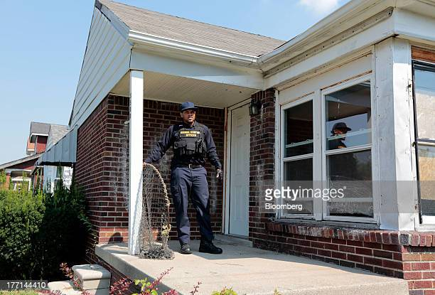 Lapez Moore an officer with the City of Detroit Animal Control stands on the porch of a home where four pit bulls were seized in Detroit Michigan US...