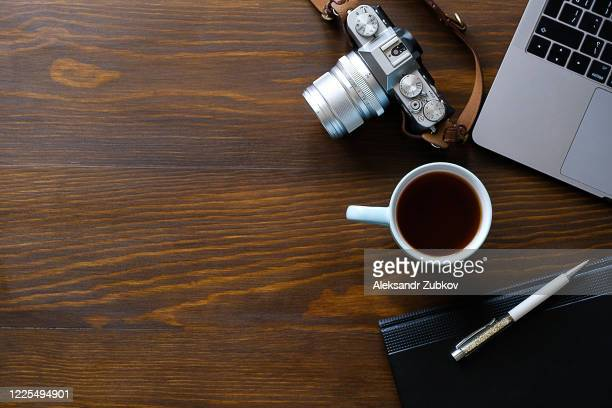 a laptop, a cup of tea, a camera, and a notepad lie on a dark wooden table. the workplace of a photographer or a freelancer. - bovenste deel stockfoto's en -beelden