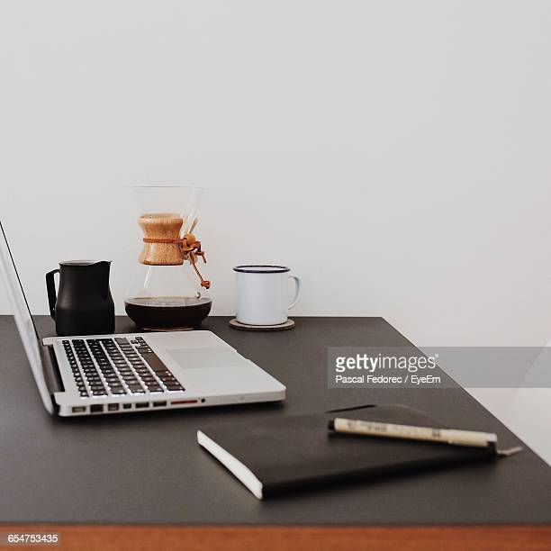 Laptop Amidst Diary And Coffee On Desk At Home Office