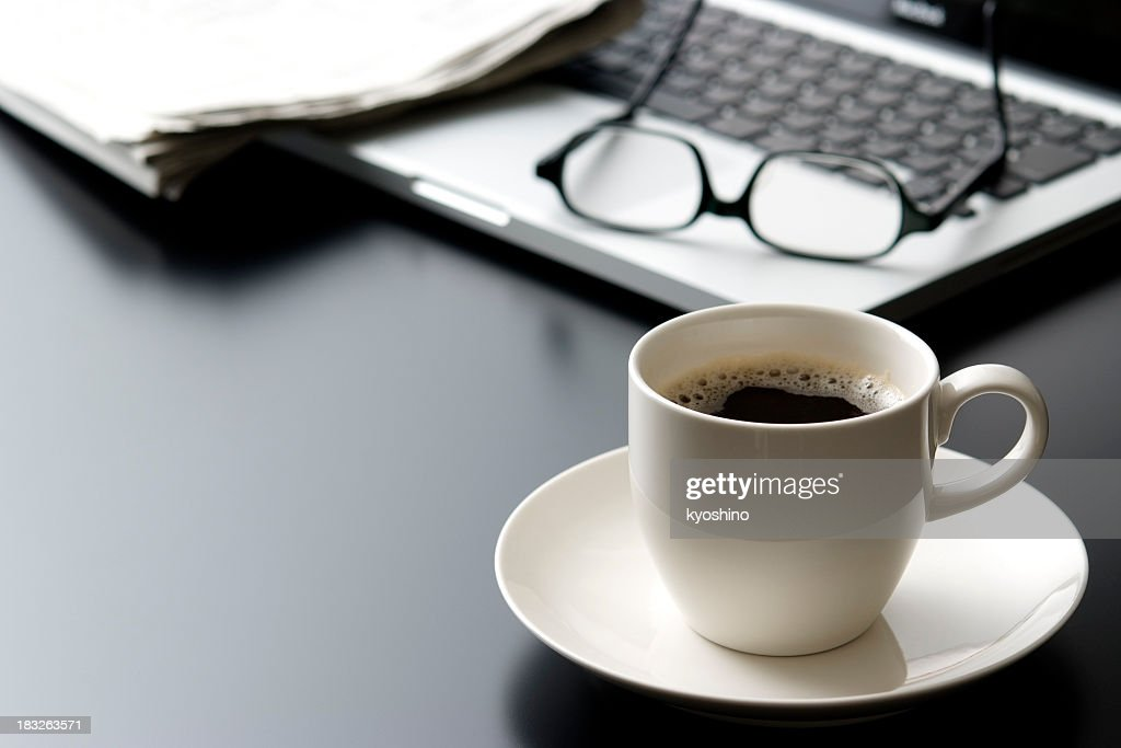 Laptop and a cup of coffee on office desk : Stock Photo