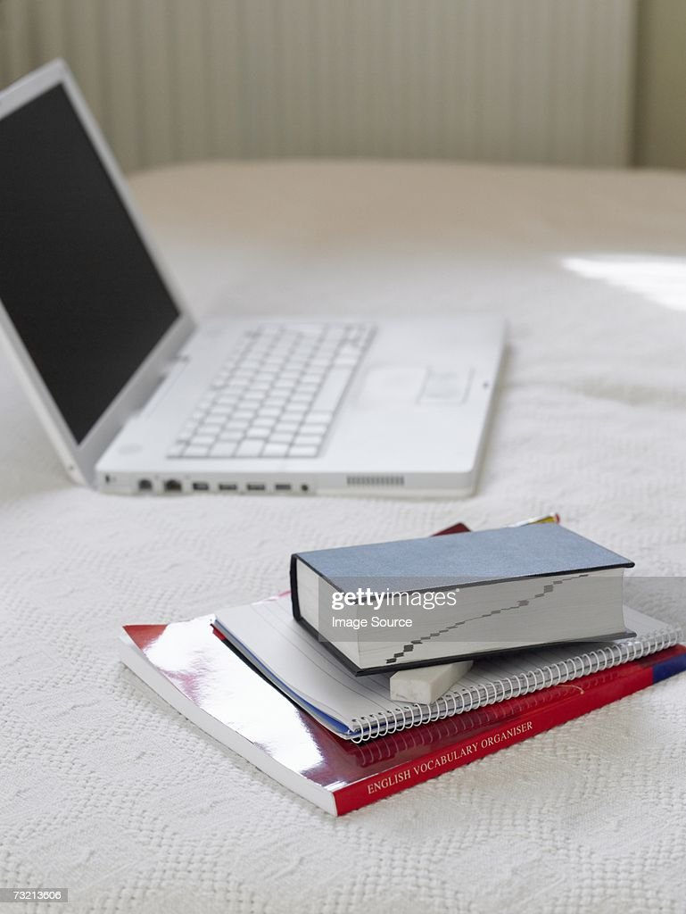 Laptop and books on bed : Stock Photo
