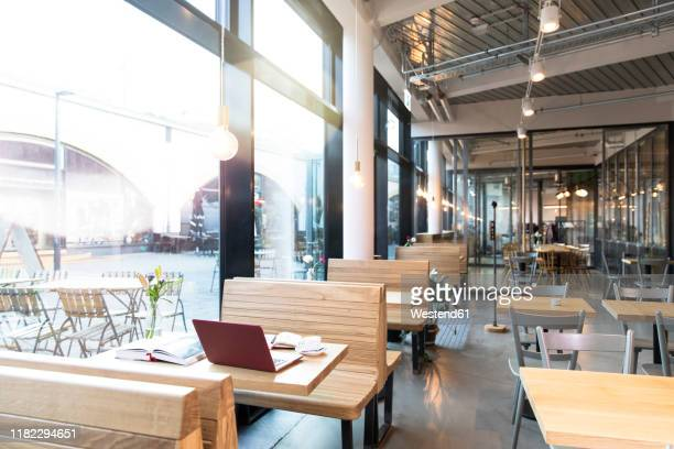 laptop and books on table in a modern cafe - サテン ストックフォトと画像