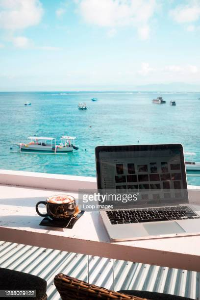Laptop and cappuccino with an ocean view.