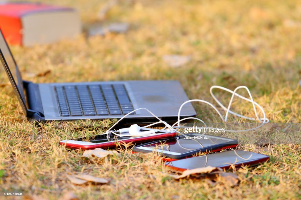 Laptop And Cell Phones Lying On Grass In The Park : Stock Photo