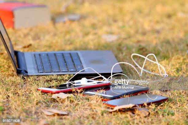 Laptop And Cell Phones Lying On Grass In The Park