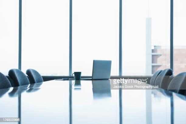 laptop and coffee cup on conference room table - conferentietafel stockfoto's en -beelden